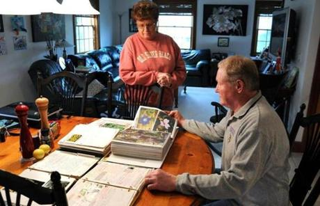 Diane and Barry Funfar look at photos of flowers of their once-flourishing gardens.